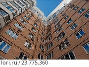 Купить «Новый высотный дом, вид снизу вверх», эксклюзивное фото № 23775360, снято 1 октября 2016 г. (c) Svet / Фотобанк Лори
