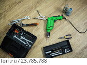 Купить «Close up of tool box and drill machine lying on floor», фото № 23785788, снято 28 июня 2016 г. (c) Wavebreak Media / Фотобанк Лори