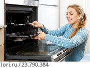 Купить «Woman placing roasting tray in kitchen oven», фото № 23790384, снято 20 сентября 2018 г. (c) Яков Филимонов / Фотобанк Лори