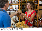 Купить «Male staff giving packed bread to woman», фото № 23790748, снято 17 мая 2016 г. (c) Wavebreak Media / Фотобанк Лори