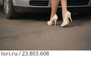 Купить «Девушка в туфлях на высоком каблуке подходит к автомобилю», видеоролик № 23803608, снято 10 октября 2016 г. (c) Илья Шаматура / Фотобанк Лори