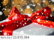 Купить «close up of christmas gift with bow over lights», фото № 23815384, снято 7 октября 2015 г. (c) Syda Productions / Фотобанк Лори