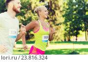 Купить «happy sportsmen couple racing wit badge numbers», фото № 23816324, снято 16 августа 2015 г. (c) Syda Productions / Фотобанк Лори