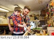 Купить «father and son with chisel working at workshop», фото № 23818084, снято 14 мая 2016 г. (c) Syda Productions / Фотобанк Лори