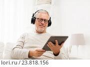 Купить «senior man with tablet pc and headphones at home», фото № 23818156, снято 7 июля 2016 г. (c) Syda Productions / Фотобанк Лори