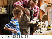 Купить «father and son with drill working at workshop», фото № 23818488, снято 14 мая 2016 г. (c) Syda Productions / Фотобанк Лори