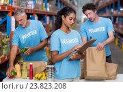 Купить «Three volunteers packing eatables in cardboard box in a warehouse», фото № 23823208, снято 23 марта 2016 г. (c) Wavebreak Media / Фотобанк Лори
