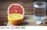 Купить «orange, grapefruit and glass of water with pills», видеоролик № 23860080, снято 18 октября 2016 г. (c) Syda Productions / Фотобанк Лори