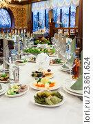 Праздничный длинный стол с холодными закусками и алкогольными напитками в ресторане. Стоковое фото, фотограф Кекяляйнен Андрей / Фотобанк Лори