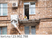 Купить «Капитальный ремонт балкона с помощью автовышки», эксклюзивное фото № 23902788, снято 3 июля 2015 г. (c) Алёшина Оксана / Фотобанк Лори