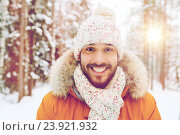 smiling young man in snowy winter forest, фото № 23921932, снято 29 декабря 2014 г. (c) Syda Productions / Фотобанк Лори