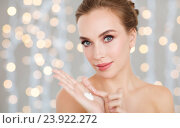 Купить «woman with moisturizing cream on hand over lights», фото № 23922272, снято 14 апреля 2016 г. (c) Syda Productions / Фотобанк Лори