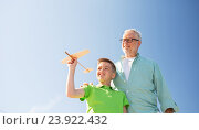 senior man and boy with toy airplane over sky, фото № 23922432, снято 9 июля 2016 г. (c) Syda Productions / Фотобанк Лори