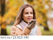 Купить «woman recording voice on smartphone in autumn park», фото № 23923140, снято 6 октября 2016 г. (c) Syda Productions / Фотобанк Лори