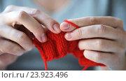 Купить «woman knitting with needles and red yarn», видеоролик № 23923496, снято 22 октября 2016 г. (c) Syda Productions / Фотобанк Лори
