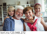 Купить «Portrait of grandparents smiling with their grandchildren», фото № 23948272, снято 1 июля 2016 г. (c) Wavebreak Media / Фотобанк Лори
