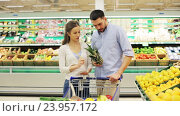 Купить «couple with food in shopping cart at grocery store», видеоролик № 23957172, снято 24 октября 2016 г. (c) Syda Productions / Фотобанк Лори