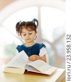 Купить «Маленькая девочка читает книгу за столом», фото № 23958132, снято 1 августа 2015 г. (c) Сергей Колесников / Фотобанк Лори