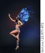Купить «Симпатичная молодая девушка в синем карнавальном костюме с перьями на темном фоне», фото № 23971472, снято 24 января 2015 г. (c) Евгений Захаров / Фотобанк Лори