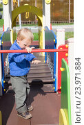 Купить «Ребенок гуляет на детской игровой площадке», фото № 23971884, снято 3 сентября 2016 г. (c) Андрей Некрасов / Фотобанк Лори