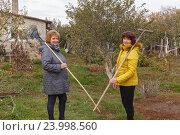 Купить «Две женщины в саду с граблями», фото № 23998560, снято 22 октября 2016 г. (c) Акиньшин Владимир / Фотобанк Лори