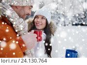 Купить «happy couple with tea cups over winter landscape», фото № 24130764, снято 23 января 2016 г. (c) Syda Productions / Фотобанк Лори