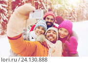 smiling friends with camera in winter forest. Стоковое фото, фотограф Syda Productions / Фотобанк Лори