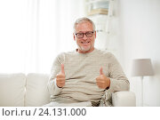 smiling senior man showing thumbs up at home. Стоковое фото, фотограф Syda Productions / Фотобанк Лори