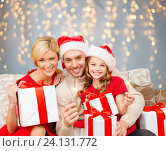 Купить «happy family holding gift boxes and sparkles», фото № 24131772, снято 26 октября 2013 г. (c) Syda Productions / Фотобанк Лори