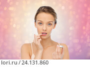 Купить «young woman applying lip balm to her lips», фото № 24131860, снято 31 октября 2015 г. (c) Syda Productions / Фотобанк Лори