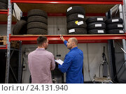 Купить «auto mechanic and man with tires at car shop», фото № 24131940, снято 1 июля 2016 г. (c) Syda Productions / Фотобанк Лори