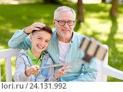 Купить «old man and boy taking selfie by smartphone», фото № 24131992, снято 9 июля 2016 г. (c) Syda Productions / Фотобанк Лори