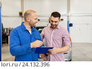 auto mechanic with clipboard and man at car shop. Стоковое фото, фотограф Syda Productions / Фотобанк Лори