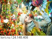 Купить «Young woman at fair near counter with Christmas gifts», фото № 24148408, снято 27 января 2020 г. (c) Яков Филимонов / Фотобанк Лори