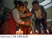 Купить «Индийская семья зажигает огонь в праздник Дивали (Индийский Новый год) в индийском культурном центре в городе Москве», фото № 24149620, снято 29 октября 2016 г. (c) Николай Винокуров / Фотобанк Лори