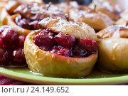 Купить «Запеченные яблоки с клюквой крупным планом», фото № 24149652, снято 8 сентября 2016 г. (c) Сергей Вольченко / Фотобанк Лори