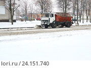 Снегоуборочная машина с ковшом чистит городские улицы в непогоду. Стоковое фото, фотограф Никита Ковалёв / Фотобанк Лори