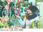 Купить «Happy smiling woman choosing Christmas decoration», фото № 24167680, снято 20 марта 2019 г. (c) Яков Филимонов / Фотобанк Лори