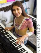 Купить «Girl choosing synthesizer in store», фото № 24182216, снято 19 августа 2018 г. (c) Яков Филимонов / Фотобанк Лори