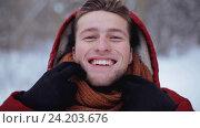Купить «happy man in winter jacket with hood outdoors», видеоролик № 24203676, снято 10 ноября 2016 г. (c) Syda Productions / Фотобанк Лори