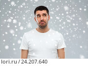 Купить «unhappy young man over snow background», фото № 24207640, снято 15 января 2016 г. (c) Syda Productions / Фотобанк Лори