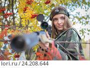 Купить «Молодая девушка в кустах рябины со снайперской винтовкой», фото № 24208644, снято 2 октября 2016 г. (c) Алексей Кокорин / Фотобанк Лори