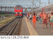 Купить «Пассажиры прогуливаются по платформе во время стоянки поезда», фото № 24210464, снято 18 июля 2016 г. (c) Иван Карпов / Фотобанк Лори
