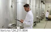 Купить «man wearing coat taking off data from equipment in winery», видеоролик № 24211804, снято 7 сентября 2016 г. (c) Яков Филимонов / Фотобанк Лори