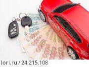 Ключ лежит на деньгах и игрушечный автомобиль. Стоковое фото, фотограф Андрей Черников / Фотобанк Лори