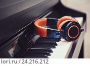Сине-оранжевые наушники на фортепианной клавиатуре. Стоковое фото, фотограф Standard Primitive / Фотобанк Лори