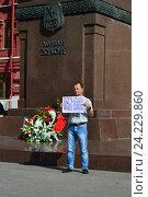 Купить «Мужчина держит плакат с надписью «Война - всего лишь трусливое бегство от проблем мирного времени» около памятника маршалу Жукову в Москве», эксклюзивное фото № 24229860, снято 9 июля 2016 г. (c) lana1501 / Фотобанк Лори