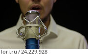 Купить «Мужчина поёт в студии перед микрофоном», видеоролик № 24229928, снято 5 октября 2016 г. (c) Pavel Biryukov / Фотобанк Лори
