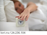 Купить «close up of woman with alarm clock in bed at home», фото № 24236104, снято 30 апреля 2016 г. (c) Syda Productions / Фотобанк Лори