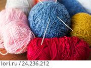 Купить «knitting needles and balls of yarn on wood», фото № 24236212, снято 20 октября 2016 г. (c) Syda Productions / Фотобанк Лори
